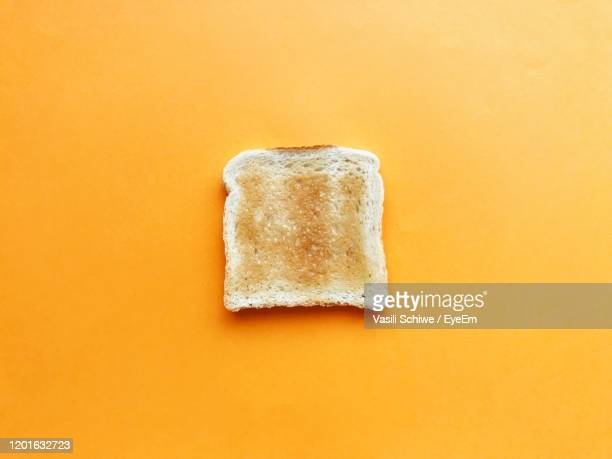 directly above shot of bread over orange background - bread stock pictures, royalty-free photos & images
