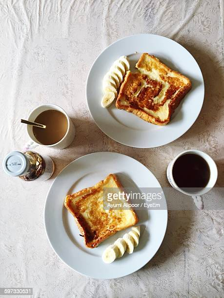 Directly Above Shot Of Breads With Banana Slices Served In Plates On Table