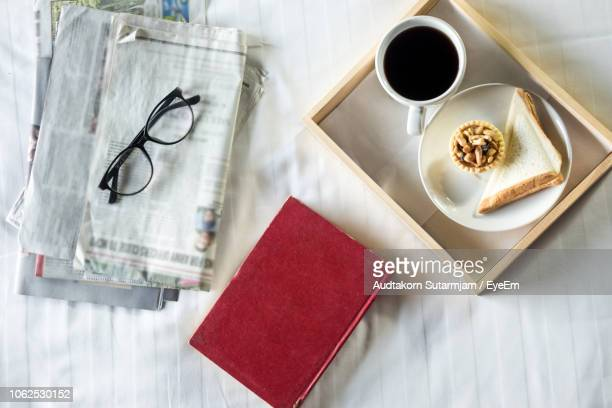 Directly Above Shot Of Breakfast With Book And Newspaper On Table