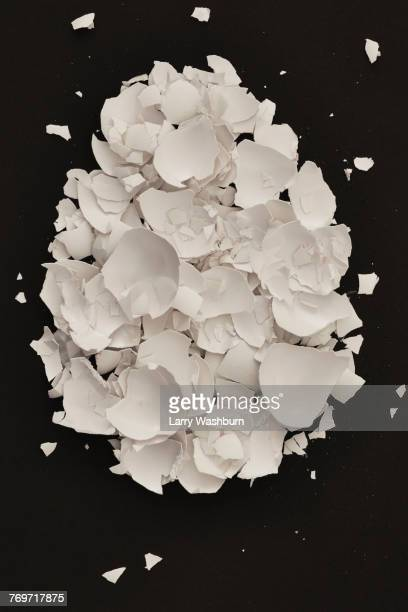 directly above shot of broken eggshell on black background - eggshell stock pictures, royalty-free photos & images