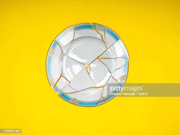 directly above shot of broken plate over yellow background - un seul objet photos et images de collection
