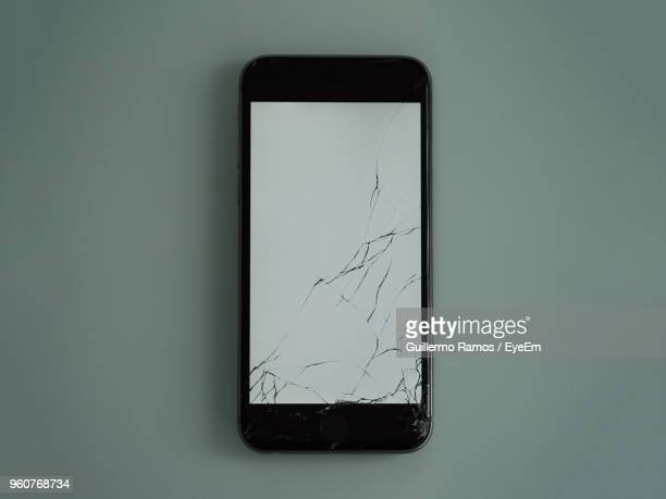 Directly Above Shot Of Broken Smart Phone On Table