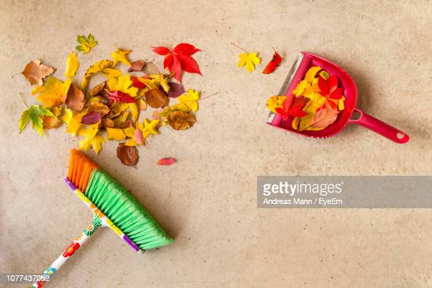 directly above shot of broom with fallen autumn leaves on floor - dustpan and brush stock pictures, royalty-free photos & images