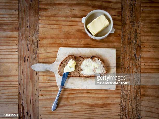 directly above shot of brown bread with butter on wooden table - spreading stock pictures, royalty-free photos & images