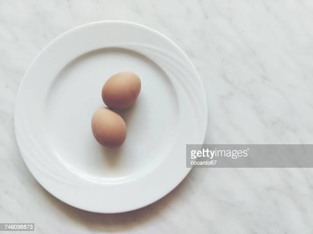 directly above shot of brown eggs in white plate - ei bruin stockfoto's en -beelden