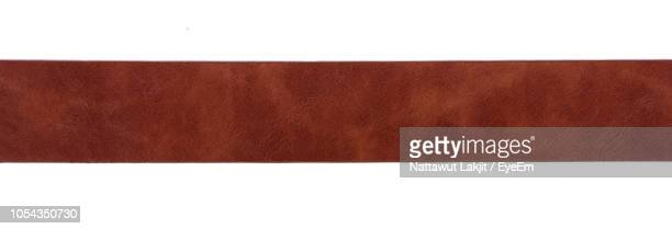 directly above shot of brown leather against white background - brown stock pictures, royalty-free photos & images