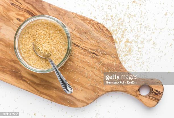 Directly Above Shot Of Brown Sugar And Cutting Board With Spoon On Table