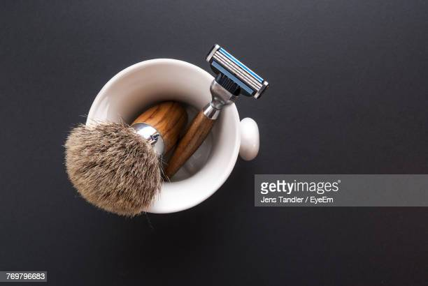 Directly Above Shot Of Brush And Razor In Container On Table