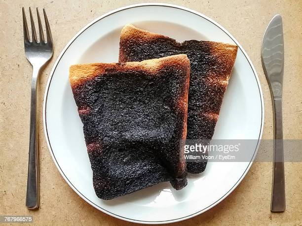 directly above shot of burnt bread in plate on table - burnt stock pictures, royalty-free photos & images