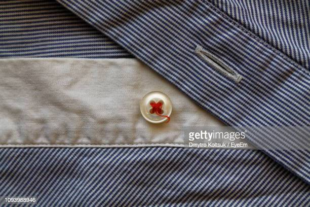 directly above shot of button on blue striped shirt - striped shirt stock pictures, royalty-free photos & images