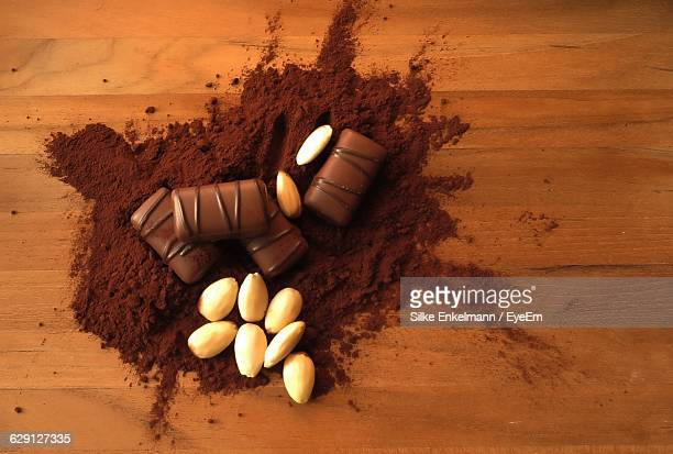 Directly Above Shot Of Cacao Powder With Almonds And Chocolates In Table