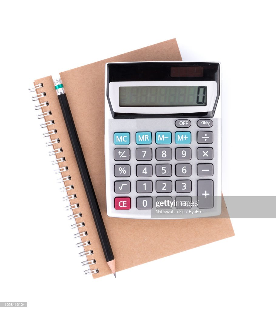 Directly Above Shot Of Calculator And Pencil On Notebook Over White Background : Stock Photo