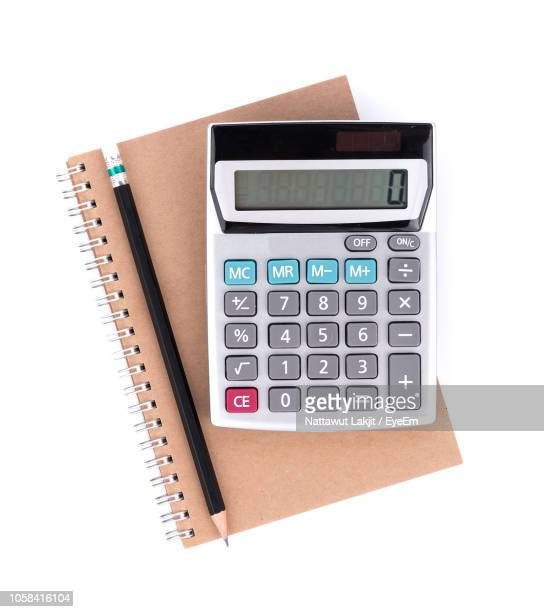 directly above shot of calculator and pencil on notebook over white background - calculator stock photos and pictures