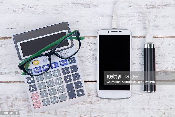 Directly Above Shot Of Calculator With Eyeglasses And Smart Phone On Table