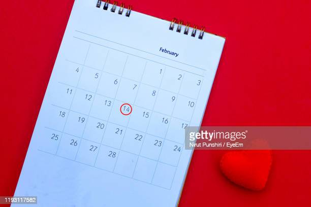 directly above shot of calendar with heart shape over red background - scadenza foto e immagini stock
