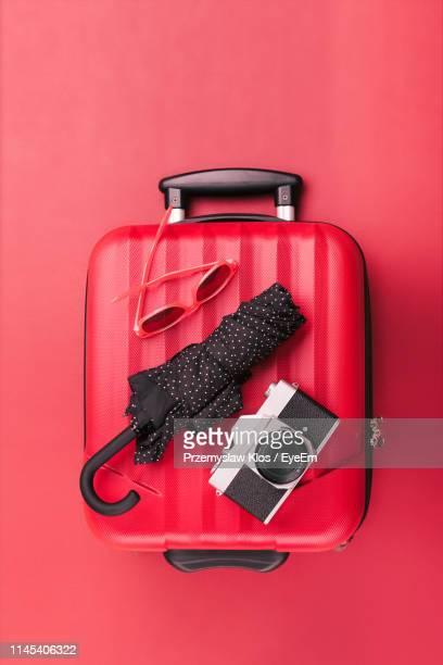 directly above shot of camera and umbrella with suitcase on red background - luggage stock pictures, royalty-free photos & images