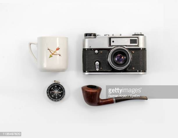 directly above shot of camera with smoking pipe and coffee mug against gray background - knolling concept stock pictures, royalty-free photos & images
