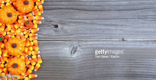directly above shot of candy corns and pumpkins on table - candy corn stock photos and pictures