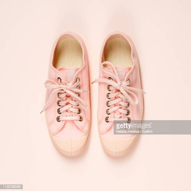 directly above shot of canvas shoes over white background - pink shoe stock pictures, royalty-free photos & images