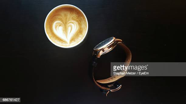 Directly Above Shot Of Cappuccino And Wristwatch On Black Table