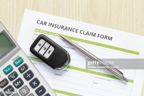 Directly Above Shot Of Car Insurance Claim Form With Key And Pen On Table