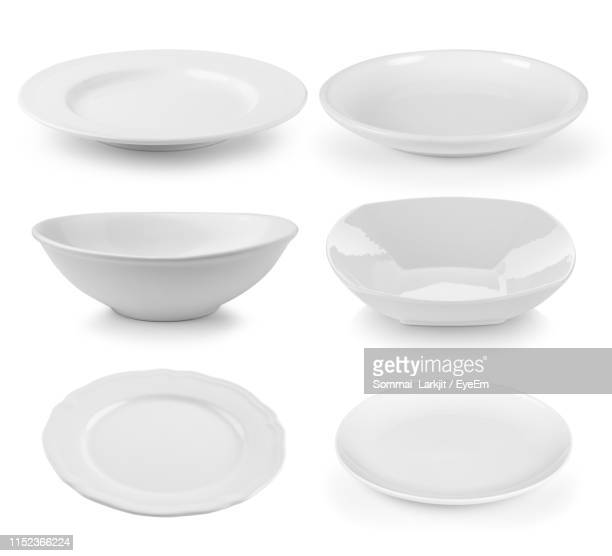 directly above shot of ceramic kitchen utensils against white background - plate stock pictures, royalty-free photos & images