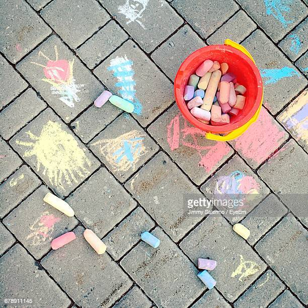 Directly Above Shot Of Chalks In Container By Drawings On Footpath
