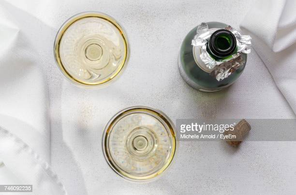 directly above shot of champagne flutes by bottle on table - champagne cork stock photos and pictures