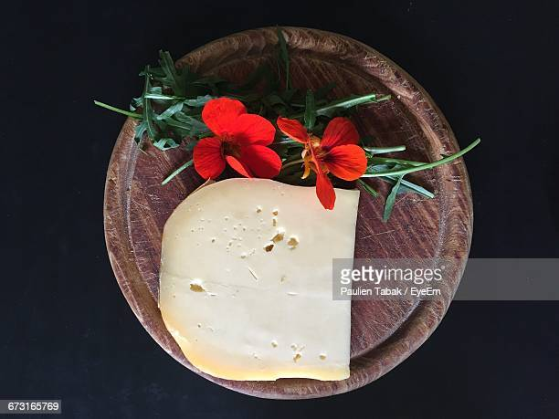 directly above shot of cheese and flowers on plate against black background - paulien tabak stock pictures, royalty-free photos & images