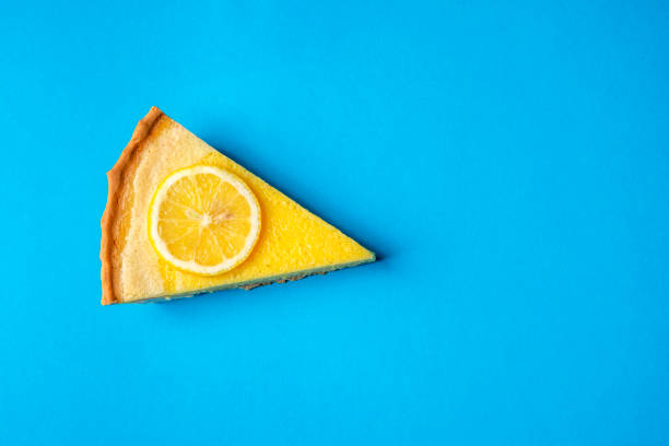 directly above shot of cheese cake slice with lemon on blue background - 芝士蛋糕 個照片及圖片檔