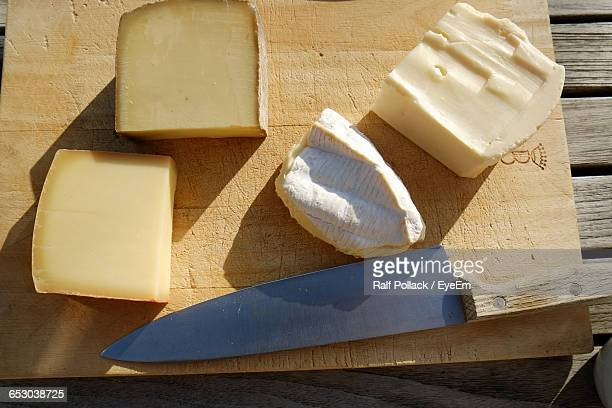 Directly Above Shot Of Cheese With Knife On Cutting Board At Table