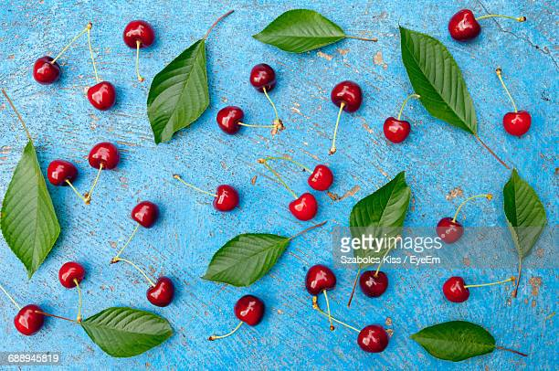 directly above shot of cherries and leaves on table - cherry kiss photos et images de collection