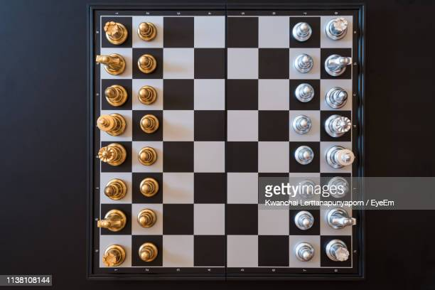 directly above shot of chess board on black background - chess stock pictures, royalty-free photos & images