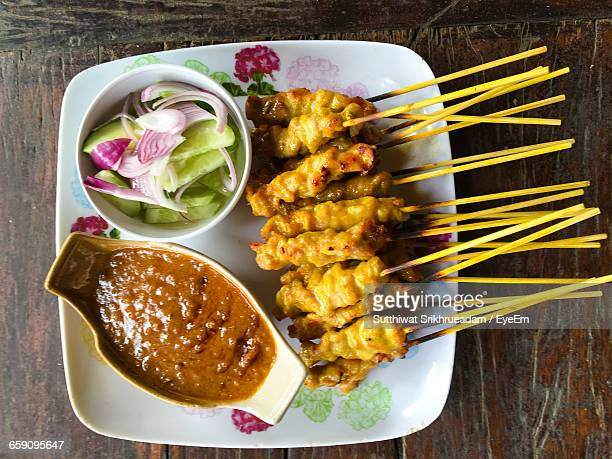 Directly Above Shot Of Chicken Satay And Salad With Gravy In Plate On Table