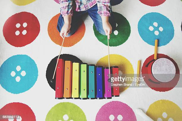 Directly Above Shot Of Child Playing Xylophone