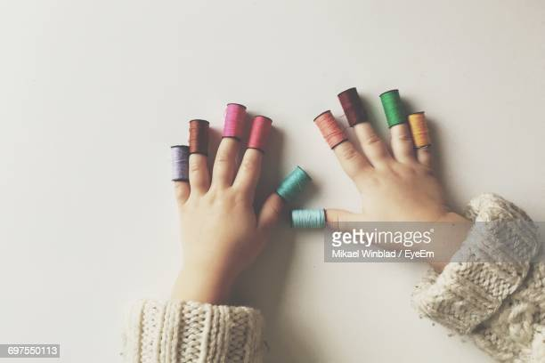 Directly Above Shot Of Child Wearing Thread Spools In Fingers On White Background