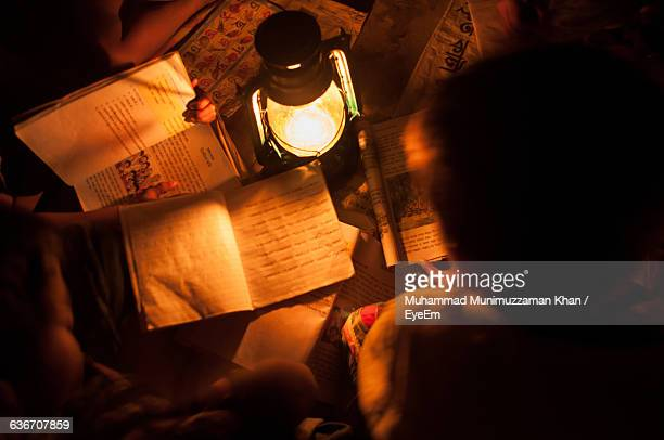 Directly Above Shot Of Children Studying With Lit Oil Lamp At Home