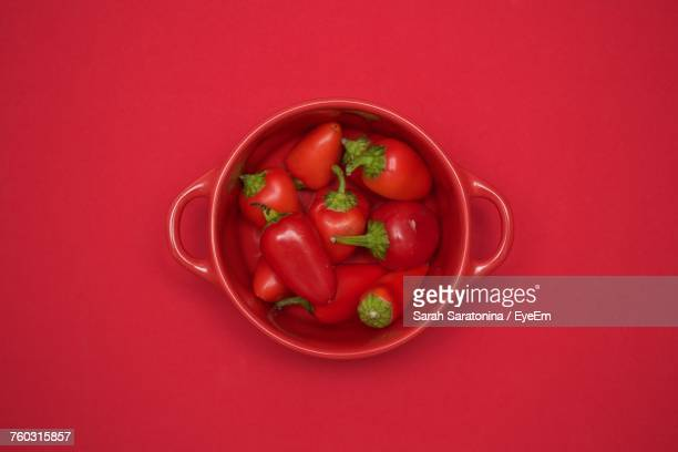 Directly Above Shot Of Chili Peppers In Bowl Against Red Background