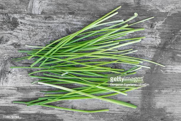 directly above shot of chives on wooden table - チャイブ ストックフォトと画像
