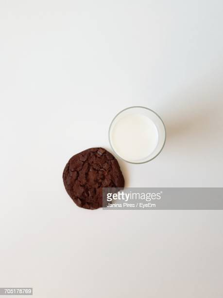 Directly Above Shot Of Chocolate Cookie And Milk In Glass On White Background
