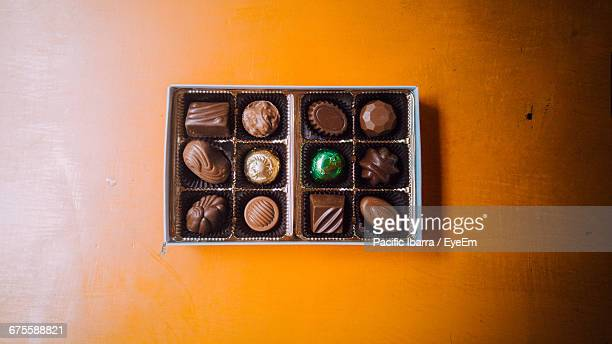 Directly Above Shot Of Chocolates In Box On Wooden Table