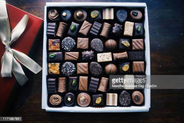 directly above shot of chocolates in tray on table - box of chocolate stock pictures, royalty-free photos & images