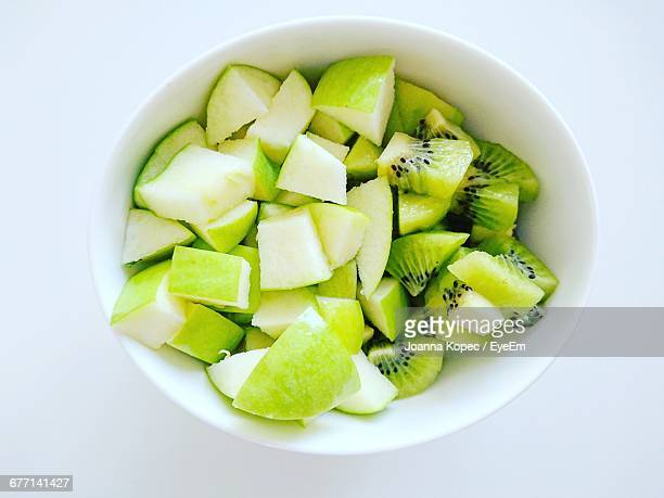Directly Above Shot Of Chopped Green Apple And Kiwi In Bowl Against White Background