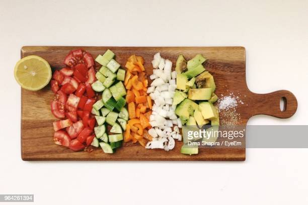 directly above shot of chopped vegetables on cutting board over white background - pimientos fotografías e imágenes de stock