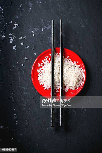 Directly Above Shot Of Chopsticks On White Rice In Plate Over Slate
