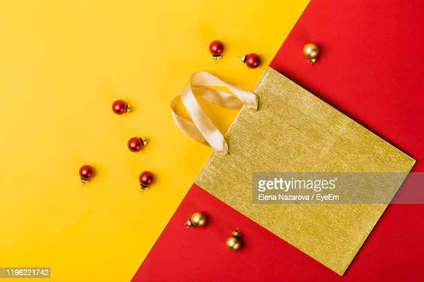 directly above shot of christmas decorations with paper bag on colored background - 取っ手 ストックフォトと画像