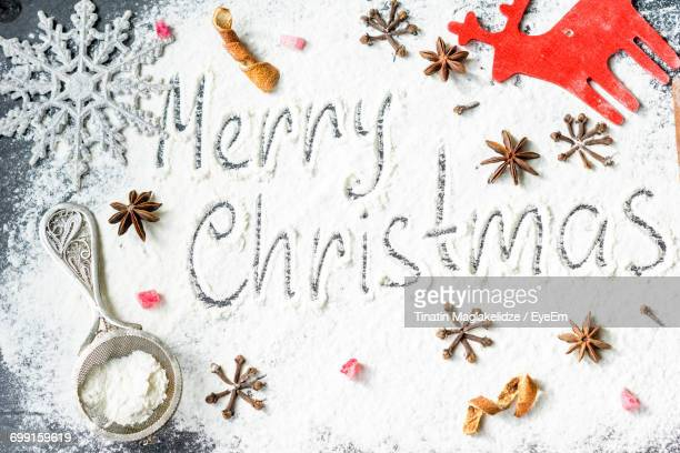 Directly Above Shot Of Christmas Greetings On Flour With Decoration And Spices At Table