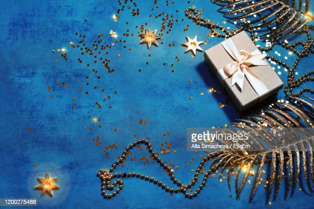 directly above shot of christmas present over blue background - ビーズ ストックフォトと画像