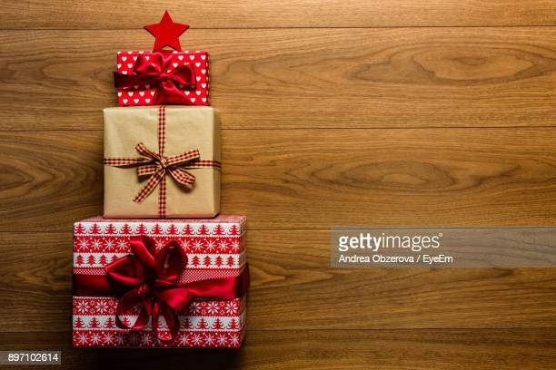 directly above shot of christmas presents on floorboard - christmas gifts stock photos and pictures