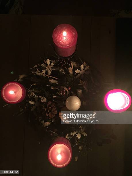 Directly Above Shot Of Christmas Wreath With Lit Candles On Table